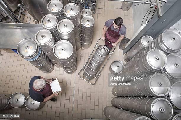 Brewers moving kegs in brewery