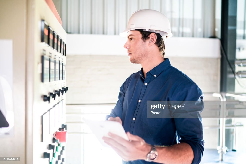 Brewery worker with tablet PC looking at machinery : Stock Photo
