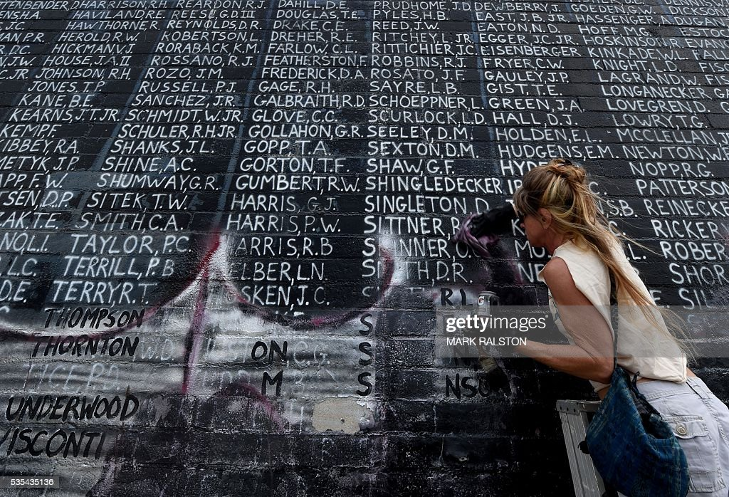 Bri Corry joins veterans and other community members to help cleanup a Veterans Memorial containing the names of 2,273 unaccounted and missing in action (MIA) Vietnam war soldiers after vandals covered the mural with silver paint graffiti prior to Memorial Day in Venice Beach, California on May 29, 2016. / AFP / Mark Ralston