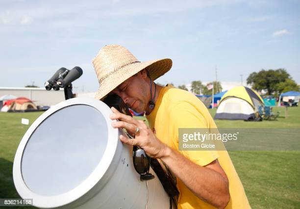 Brian Badgett of Louisville positions his camera inside a telescope so that he can photograph tomorrow's eclipse from a makeshift campground in...