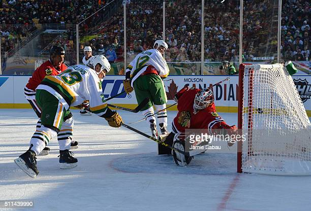 Brian Bellows of the Minnesota North Stars Alumni scores against goaltender Murray Bannerman of the Chicago Blackhawks Alumni as Chris Chelios of the...
