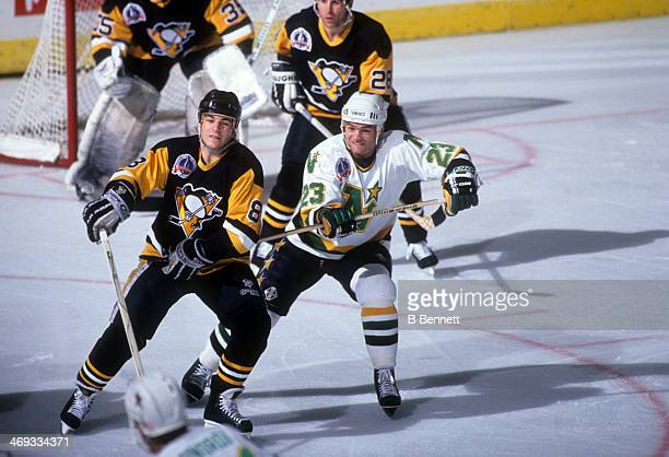 Brian Bellows of the Minnesota North Stars hooks Mark Recchi of the Pittsburgh Penguins during the 1991 Stanley Cup Finals in May 1991 at the Met...