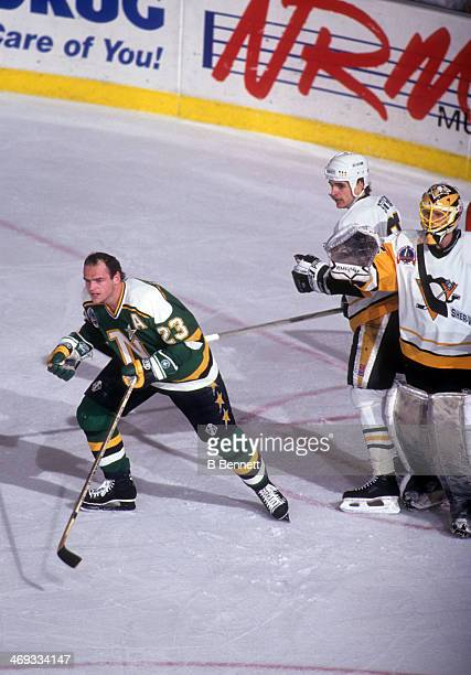 Brian Bellows of the Minnesota North Stars skates away from the crease after getting his helmet knocked off by Kevin Stevens of the Pittsburgh...