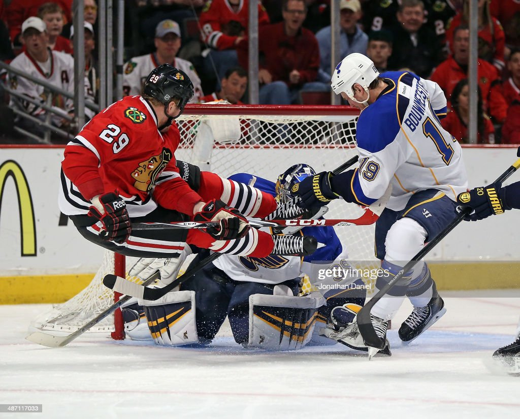 Brian Bickell of the Chicago Blackhawks goes airbourne after taking a shot against Ryan Miller and Jay Bouwmeester of the St Louis Blues in Game Six...