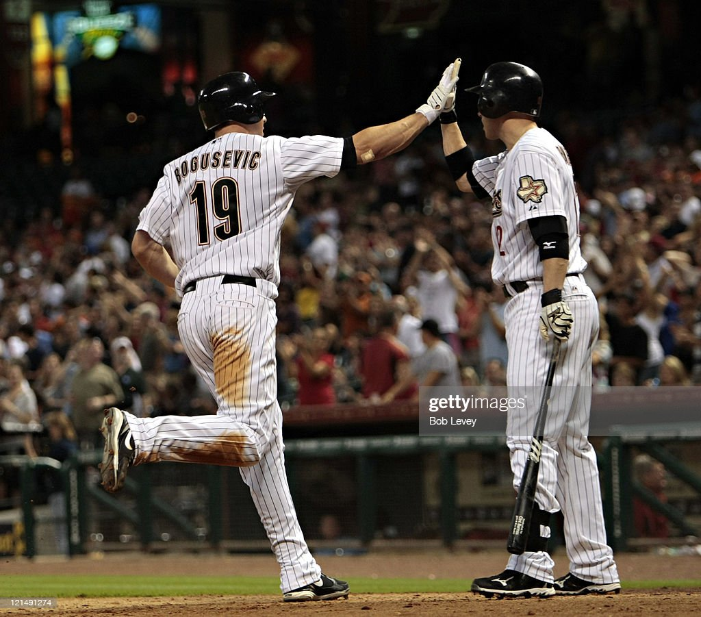 Brian Bogusevic #19 of the Houston Astros receives a high five from <a gi-track='captionPersonalityLinkClicked' href=/galleries/search?phrase=Clint+Barmes&family=editorial&specificpeople=208223 ng-click='$event.stopPropagation()'>Clint Barmes</a> #12 in the eighth inning after hitting a home run against the San Francisco Giants at Minute Maid Park on August 19, 2011 in Houston, Texas.