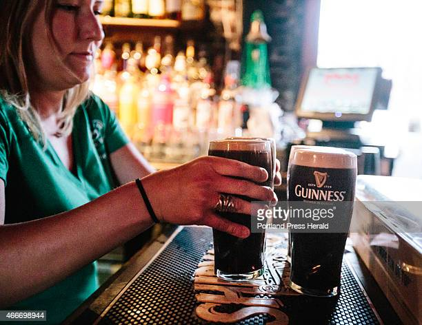 Brian Boru bartender Nicole Parker places pints of Guinness along the bar during the St Patrick's Day celebration at Brian Boru in Portland ME on...