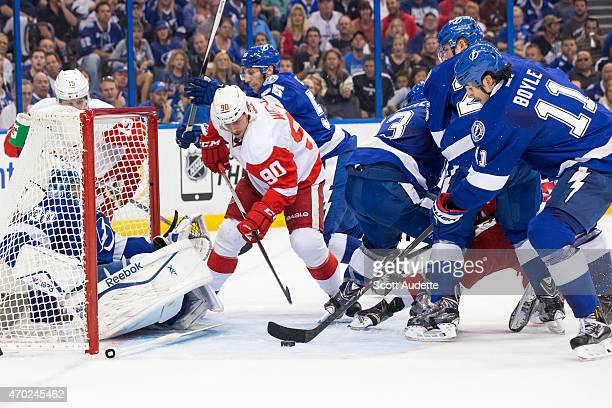 Brian Boyle clears the puck away from the goal after goalie Ben Bishop of the Tampa Bay Lightning was knocked into the net by Stephen Weiss of the...