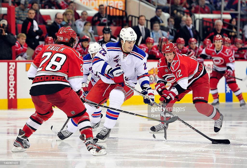 Brian Boyle #22 of the New York Rangers moves the puck between Justin Faulk #28 and <a gi-track='captionPersonalityLinkClicked' href=/galleries/search?phrase=Eric+Staal&family=editorial&specificpeople=202199 ng-click='$event.stopPropagation()'>Eric Staal</a> #12 of the Carolina Hurricanes during play at the RBC Center on March 1, 2012 in Raleigh, North Carolina.