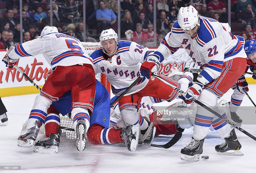 Brian Boyle #22 of the New York Rangers prepares to pick up a loose puck as teammates Dan Girardi #5 and <a gi-track='captionPersonalityLinkClicked' href=/galleries/search?phrase=Ryan+Callahan&family=editorial&specificpeople=809690 ng-click='$event.stopPropagation()'>Ryan Callahan</a> #24 fall into their net during the NHL game against the Montreal Canadiens on March 30, 2013 at the Bell Centre in Montreal, Quebec, Canada.