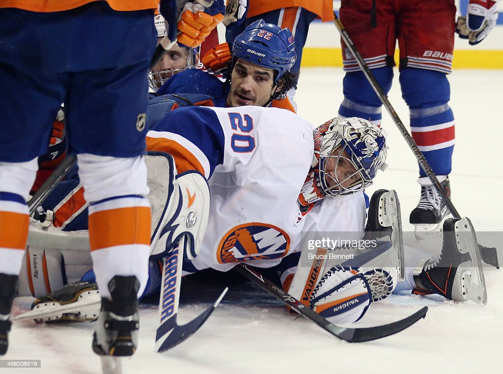 Brian Boyle #22 of the New York Rangers slides into <a gi-track='captionPersonalityLinkClicked' href=/galleries/search?phrase=Evgeni+Nabokov&family=editorial&specificpeople=171380 ng-click='$event.stopPropagation()'>Evgeni Nabokov</a> #20 of the New York Islanders during the second period at Madison Square Garden on December 20, 2013 in New York City.