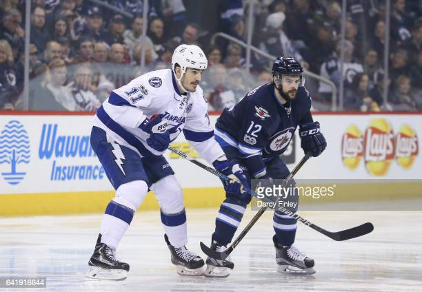 Brian Boyle of the Tampa Bay Lightning and Drew Stafford of the Winnipeg Jets get set during a first period faceoff at the MTS Centre on February 11...