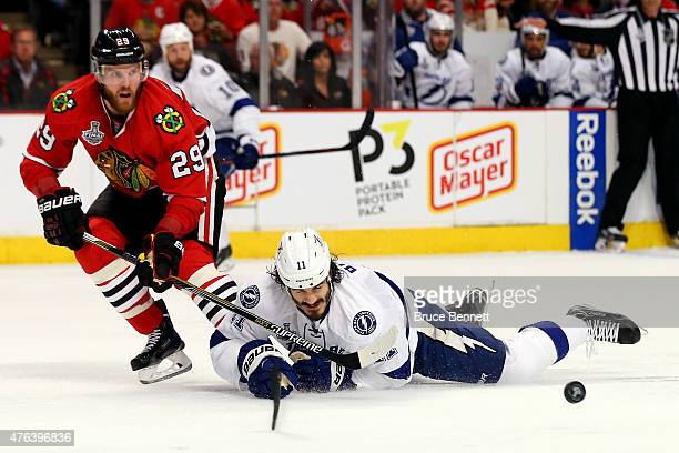 Brian Boyle of the Tampa Bay Lightning dives for a puck in the second period against Bryan Bickell of the Chicago Blackhawks during Game Three of the...