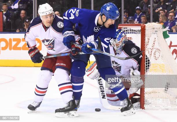 Brian Boyle of the Toronto Maple Leafs looks for the puck as Joonas Korpisalo of the Columbus Blue Jackets makes a save and Jack Johnson of the...