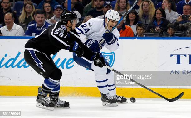 Brian Boyle of the Toronto Maple Leafs shoots past Jake Dotchin of the Tampa Bay Lightning during the first period at the Amalie Arena on March 16...