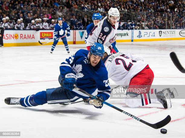 Brian Boyle of the Toronto Maple Leafs tries to keep the puck away from William Karlsson and Josh Anderson of the Columbus Blue Jackets during the...