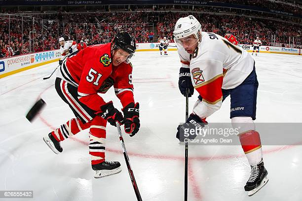 Brian Campbell of the Chicago Blackhawks and Reilly Smith of the Florida Panthers chase the puck in the third period at the United Center on November...