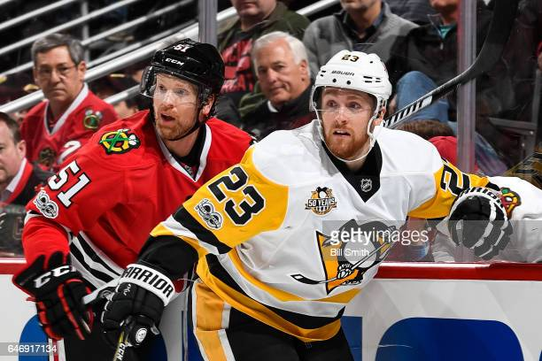 Brian Campbell of the Chicago Blackhawks and Scott Wilson of the Pittsburgh Penguins watch for the puck in the second period at the United Center on...