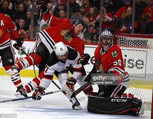 Brian Campbell of the Chicago Blackhawks flips in the air after colliding with Kyle Palmieri of the New Jersey Devils next to Corey Crawford at the...