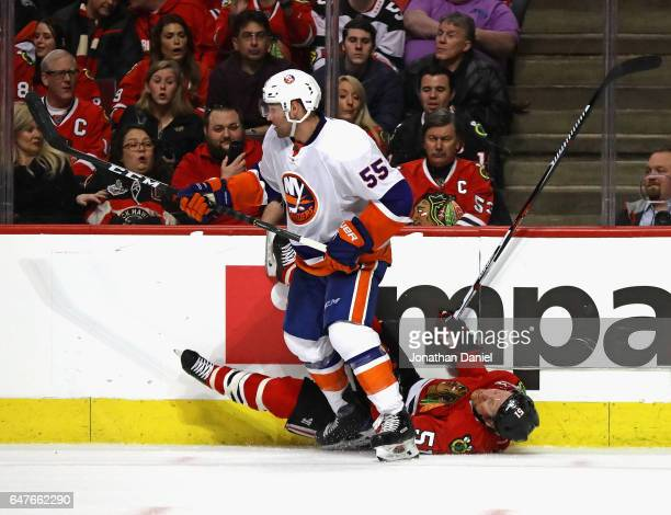 Brian Campbell of the Chicago Blackhawks hits the ice after colliding with Johnny Boychuk of the New York Islanders at the United Center on March 3...