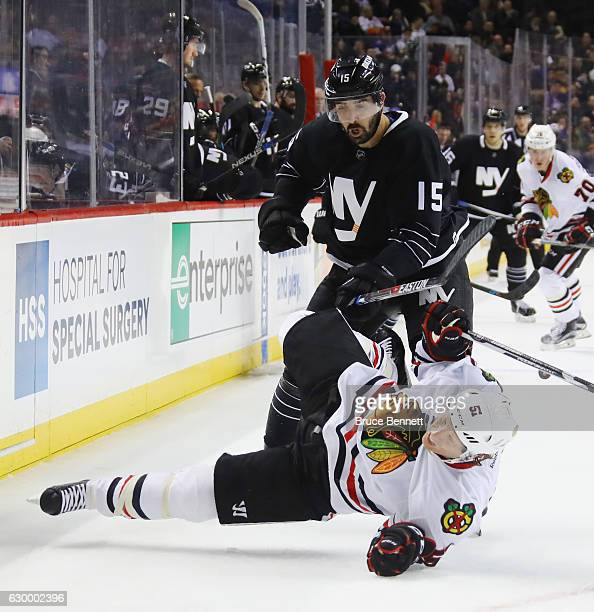 Brian Campbell of the Chicago Blackhawks is checked by Cal Clutterbuck of the New York Islanders during the second period at the Barclays Center on...