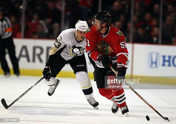 Brian Campbell of the Chicago Blackhawks looks to pass as Ryan Craig of the Pittsburgh Penguins closes in at the United Center on February 20 2011 in...