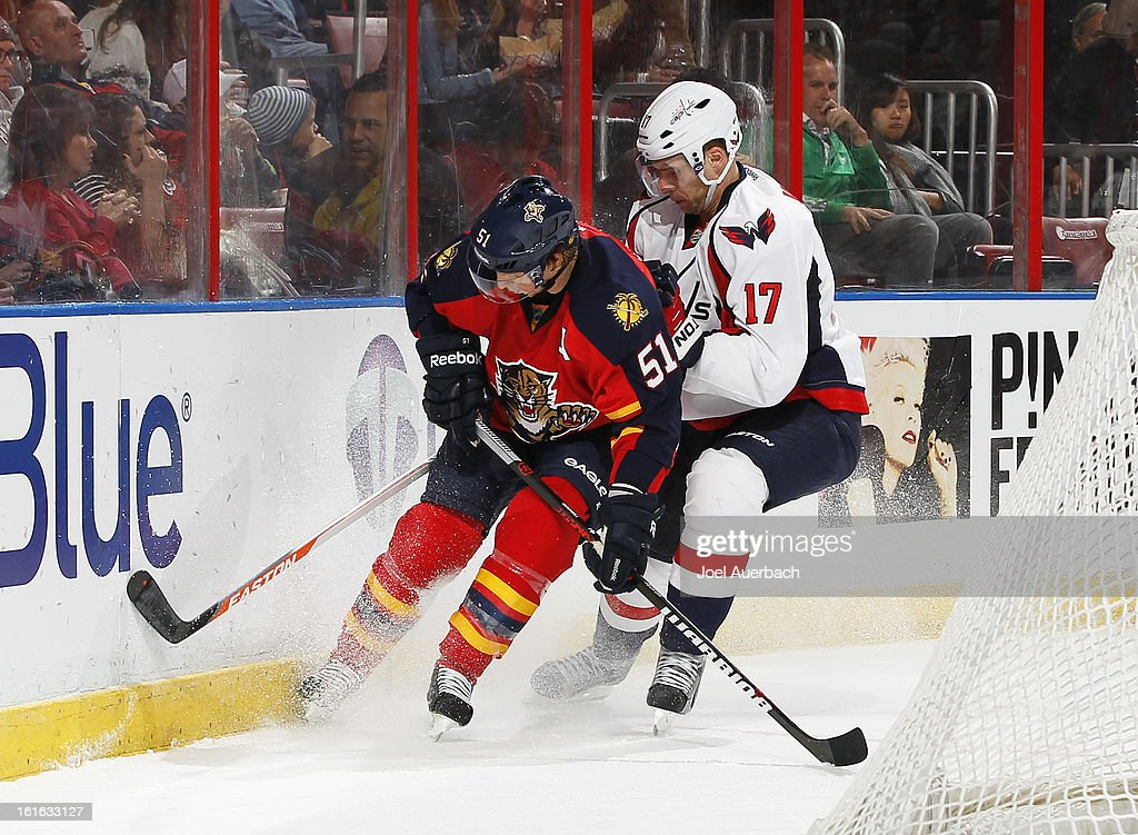 Brian Campbell #51 of the Florida Panthers and Wojtek Wolski #17 of the Washington Capitals battle for a loose puck behind the net at the BB&T Center on February 12, 2013 in Sunrise, Florida. The Capitals defeated the Panthers 6-5 in overtime.