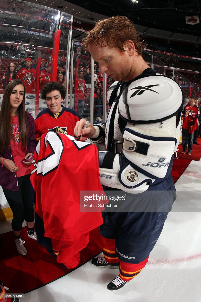 Brian Campbell #51 of the Florida Panthers autographs the jersey off his back to a fan after the final game of the season against the Columbus Blue Jackets at the BB&T Center on April 12, 2014 in Sunrise, Florida.