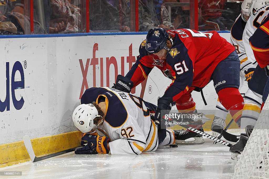 Brian Campbell #51 of the Florida Panthers checks Marcus Foligno #82 of the Buffalo Sabres as the puck comes loose at the BB&T Center on October 25, 2013 in Sunrise, Florida.