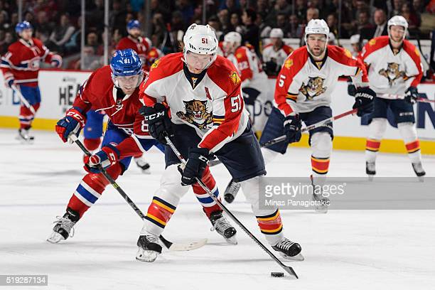 Brian Campbell of the Florida Panthers skates the puck against Lars Eller of the Montreal Canadiens in his one thousandth NHL career game at the Bell...