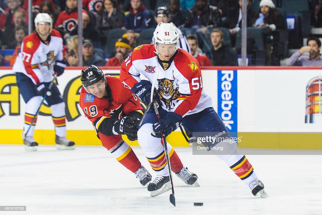 Brian Campbell #51 of the Florida Panthers skates with the puck past the defense of Blair Jones #19 of the Calgary Flames during an NHL game at Scotiabank Saddledome on November 22, 2013 in Calgary, Alberta, Canada. The Flames defeated the Panthers 4-3 in shootout.