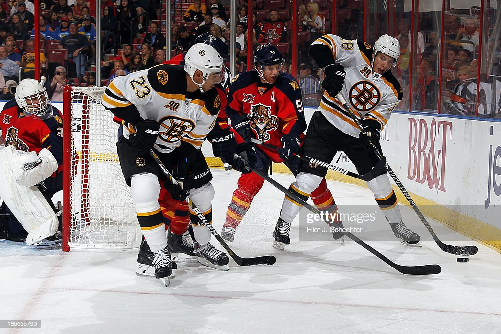 Brian Campbell of the Florida Panthers tangles with Chris Kelly of the Boston Bruins and teammate Jordan Caron at the BBT Center on October 17 2013...