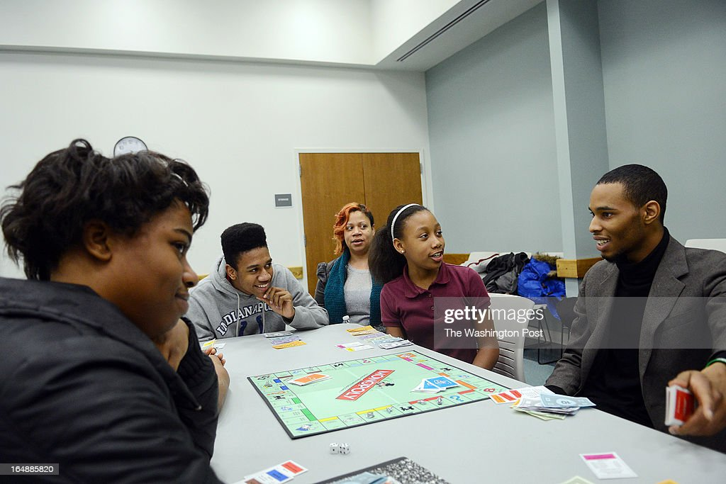 Brian Carrington, right, volunteers to teach Briana Etienne, 18, left, Deonte Harris, 17, second from left, son of Tiffany Smith, third from left, and her daughter Mikayla Smith, 11, second from right, monopoly at the Spaulding Library. Ms. Smith has brought her children to the monopoly evening ever since it started in January of this year.