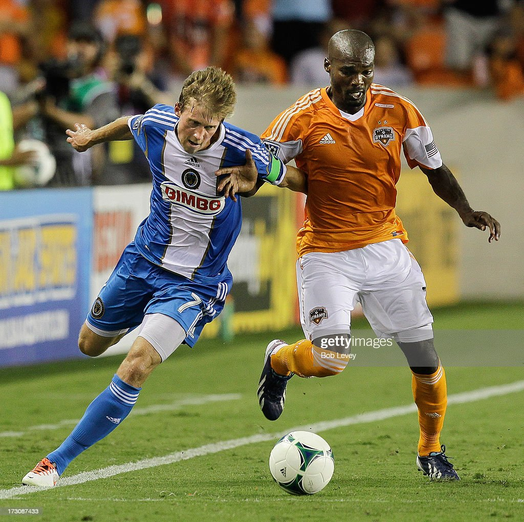 Brian Carroll of the Philadelphia Union and Omar Cummings of the Houston Dynamo battle for the ball at BBVA Compass Stadium on July 6 2013 in Houston...