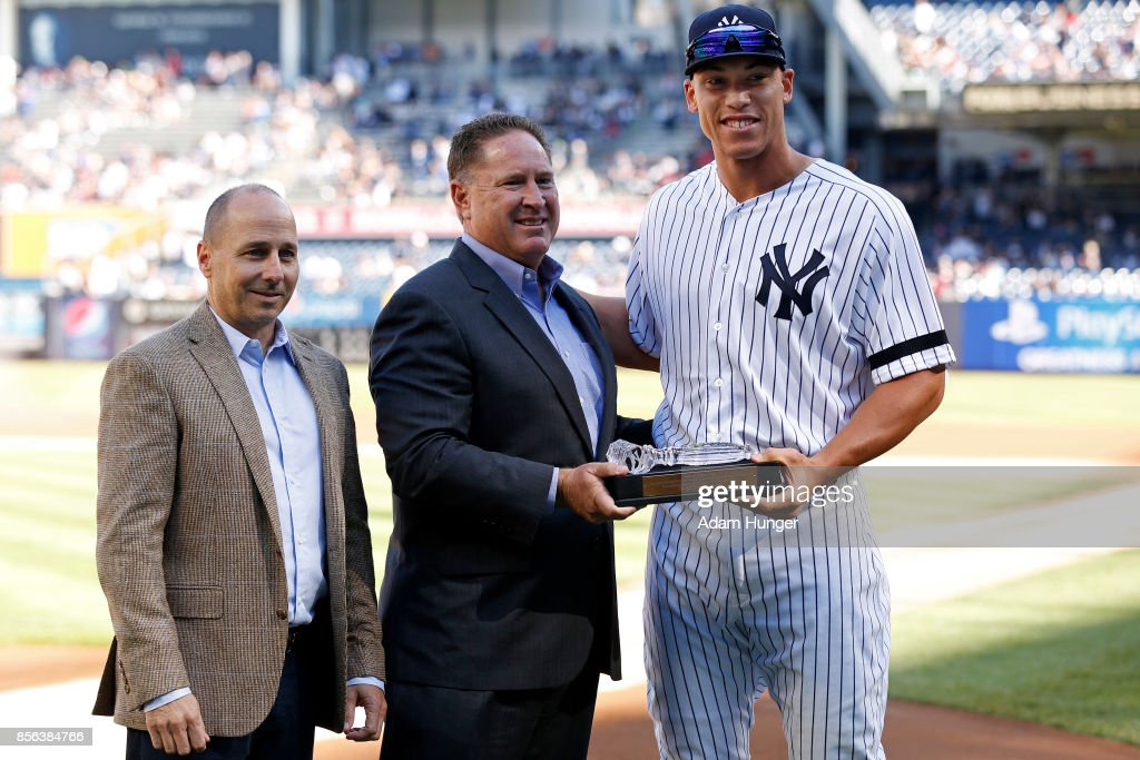 Brian Cashman general manager of the New York Yankees, left, and Damon Oppenheimer amateur scouting director of the New York Yankees, center, present Aaron Judge of the New York Yankees with a crystal gavel before the Yankees final regular season baseball game against the Toronto Blue Jays at Yankee Stadium on October 1, 2017 in the Bronx borough of New York City.