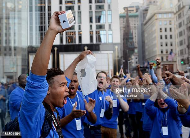 Brian Ceballo emerges from the Apple Store on Fifth Avenue as the first to purchase the new iPhone 5 to the cheers of Apple store employees September...