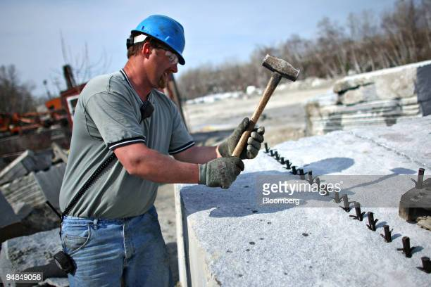 Brian Chaffee prepares a piece of granite for splitting outside a Rock of Ages Corp quarry in Graniteville Vermont US on Tuesday April 22 2008 Rock...