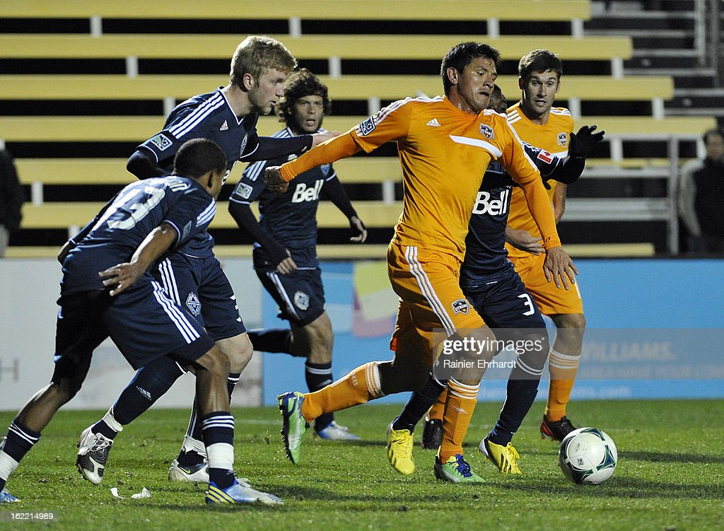 Brian Ching #25 of the Houston Dynamo battles for the ball against Vancouver Whitecaps FC defenders during the second half of a game on February 20, 2013 in Charleston, North Carolina.