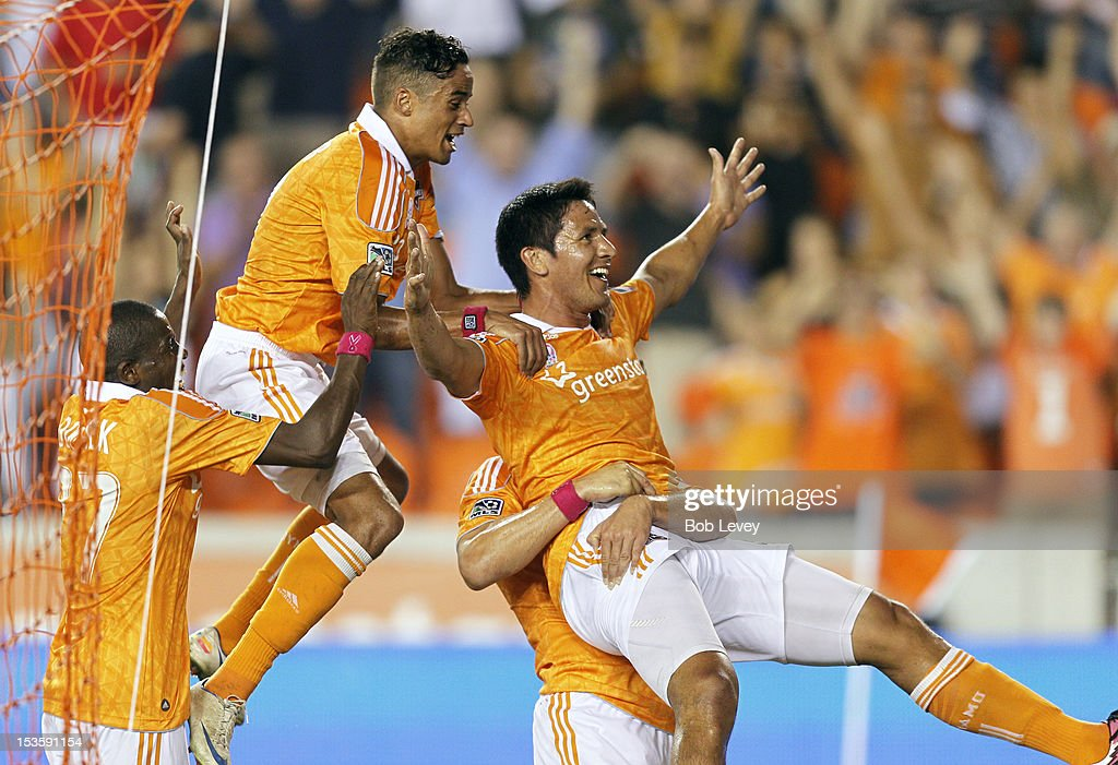 Brian Ching of the Houston Dynamo celebrates with Calen Carr and Boniek Garcia after what he thought was the go ahead goal in extra time against the...