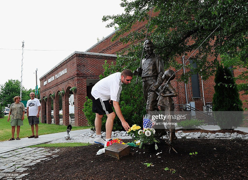 Brian Clay of Beckley, West Virginia, leaves flowers next to a statue outside of the Andy Griffith Museum in remembrance of actor Andy Griffith on July 3, 2012 in Mt Airy, North Carolina. Griffith died around 7am at his North Carolina home at age 86.