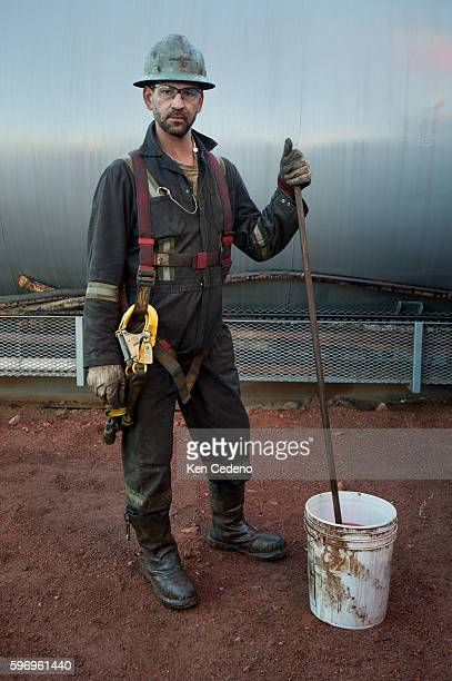 Brian Coffey a floor hand stops for a moment to pose for a photo while cleaning the tops of a storage tank at the Raven Oil Drilling rig grounds near...