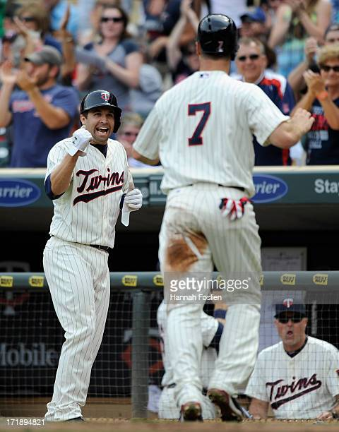 Brian Dozier and Joe Mauer of the Minnesota Twins celebrate scoring against the Kansas City Royals during the first inning of the game on June 29...