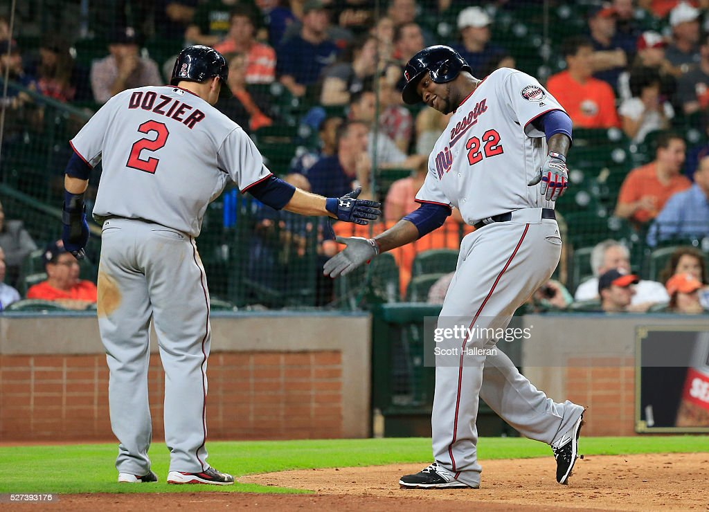 Brian Dozier and Miguel Sano of the Minnesota Twins celebrate after Sano scored a run in the fifth inning of their game against the Houston Astros at...