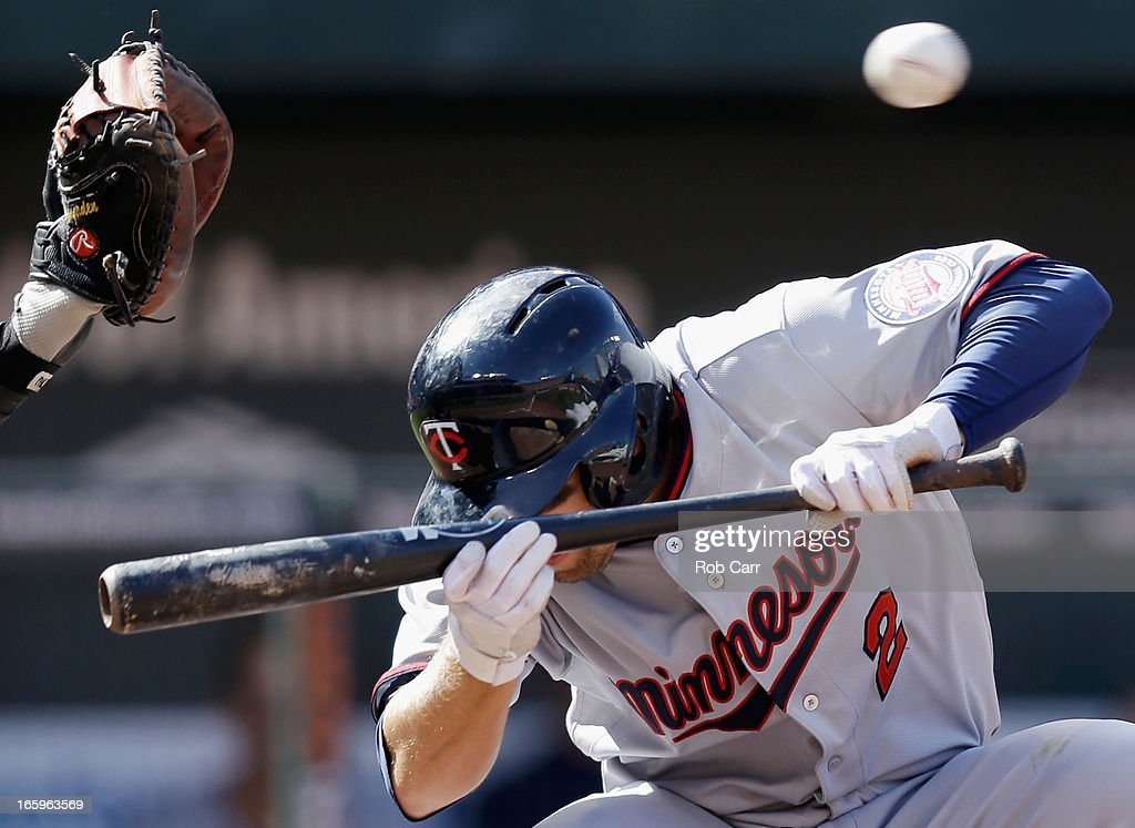 <a gi-track='captionPersonalityLinkClicked' href=/galleries/search?phrase=Brian+Dozier&family=editorial&specificpeople=7553002 ng-click='$event.stopPropagation()'>Brian Dozier</a> #2 of the Minnesota Twins avoids being hit by a pitch while attemptiing to bunt during the fifth inning against the Baltimore Orioles at Oriole Park at Camden Yards on April 7, 2013 in Baltimore, Maryland.