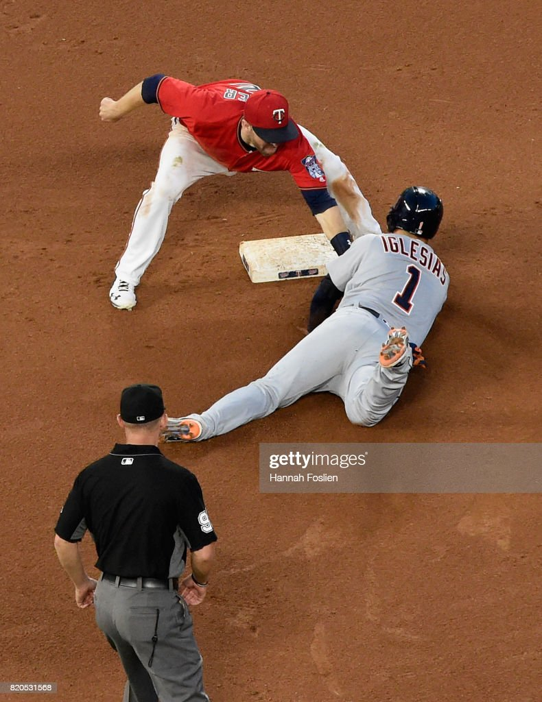 Brian Dozier #2 of the Minnesota Twins catches Jose Iglesias #1 of the Detroit Tigers stealing second base as umpire Will Little #93 looks on during the fourth inning of the game on July 21, 2017 at Target Field in Minneapolis, Minnesota. The Tigers defeated the Twins 6-3.
