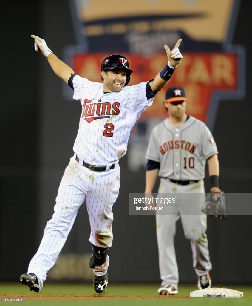 <a gi-track='captionPersonalityLinkClicked' href=/galleries/search?phrase=Brian+Dozier&family=editorial&specificpeople=7553002 ng-click='$event.stopPropagation()'>Brian Dozier</a> #2 of the Minnesota Twins celebrates a walk off single as Jake Elmore #10 of the Houston Astros looks on during the thirteenth inning of the game on August 2, 2013 at Target Field in Minneapolis, Minnesota. The Twins defeated the Astros 4-3 in thirteen inning.