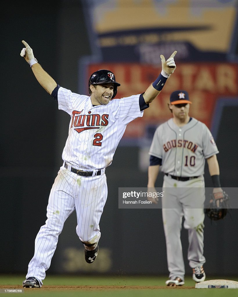 Brian Dozier #2 of the Minnesota Twins celebrates a walk-off single as Jake Elmore #10 of the Houston Astros looks on after the game on August 2, 2013 at Target Field in Minneapolis, Minnesota.