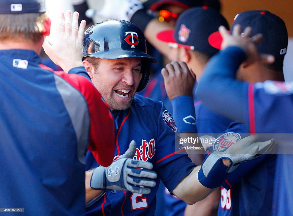 Brian Dozier of the Minnesota Twins celebrates in the dugout after scoring a run in the ninth inning against the New York Yankees at Yankee Stadium...