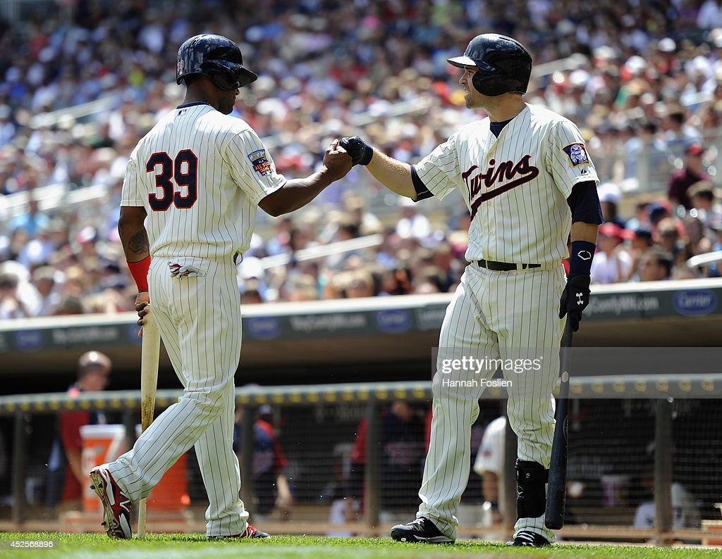 <a gi-track='captionPersonalityLinkClicked' href=/galleries/search?phrase=Brian+Dozier&family=editorial&specificpeople=7553002 ng-click='$event.stopPropagation()'>Brian Dozier</a> #2 of the Minnesota Twins congratulates teammate <a gi-track='captionPersonalityLinkClicked' href=/galleries/search?phrase=Danny+Santana&family=editorial&specificpeople=6602314 ng-click='$event.stopPropagation()'>Danny Santana</a> #39 on scoring a run against the Cleveland Indians during the third inning of the game on July 23, 2014 at Target Field in Minneapolis, Minnesota. The Twins defeated the Indians 3-1.