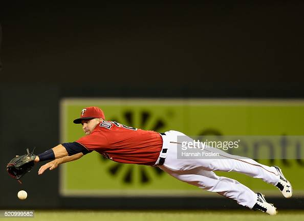 Brian Dozier of the Minnesota Twins dives for a single hit by Jimmy Rollins of the Chicago White Sox during the sixth inning of the game on April 13...