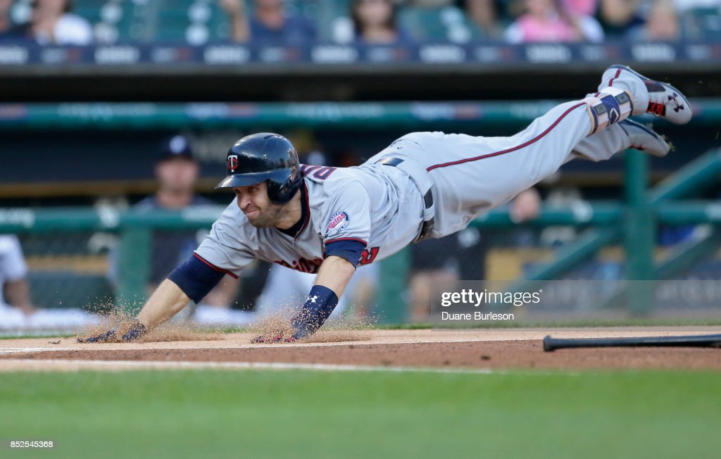 Brian Dozier #2 of the Minnesota Twins dives into home plate to score on a bunt grounder and a throwing error by third baseman Jeimer Candelario #46 of the Detroit Tigers during the first inning at Comerica Park on September 23, 2017 in Detroit, Michigan. Candelario tried to throw out Dozier at first base but the ball went into right field.